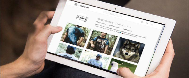 Manos en tablet navegando instagram de Okapi Clothing