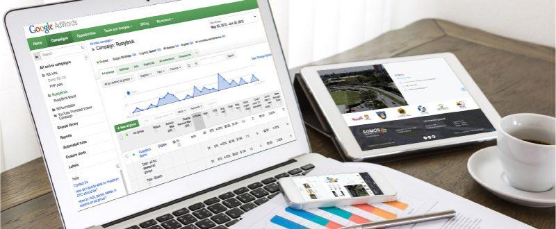 Computador portatil y tablet observando la interfaz de Google Adwords